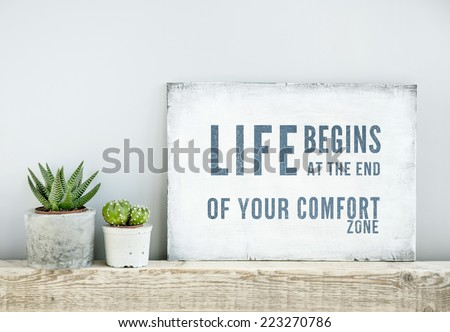 motivational poster quote LIFE BEGINS AT THE END OF COMFORT ZONE. scandinavian or american style room interior. - stock photo