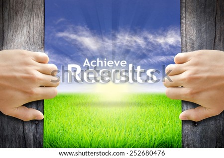 "Motivational quotes ""Achieve results"" . Hands opening a wooden door then found a texts floating among new world as green grass field, Blue sky and the Sunrise. - stock photo"