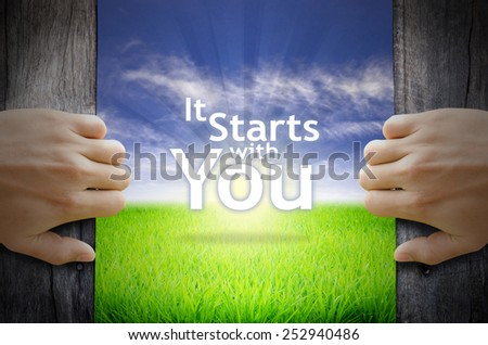 "Motivational quotes ""It starts with You"" . Hands opening a wooden door then found a texts floating among new world as green grass field, Blue sky and the Sunrise. - stock photo"