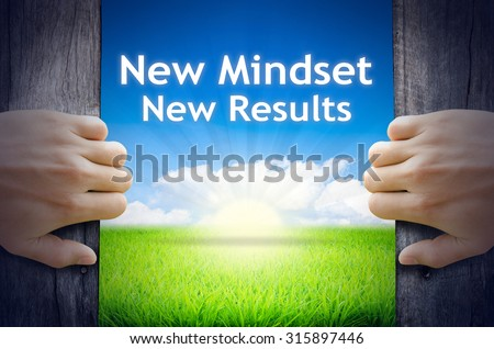 """Motivational quotes """"New Mindset New Results"""" . Hands opening a wooden door then found a texts floating among new world as green grass field, Blue sky and the Sunrise. - stock photo"""