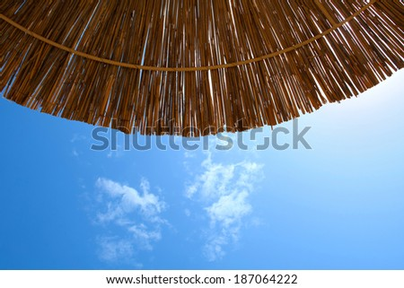 motive of marine: reed umbrellas on the beach, on a background of sky and clouds