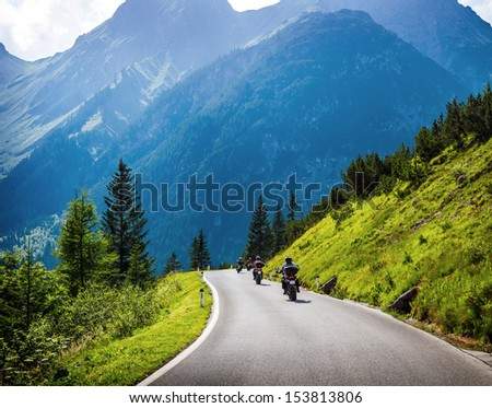Moto racers riding on mountainous road, drive a motorcycle, summer adventure, extreme sport, travel to Europe, active lifestyle, vacation concept  - stock photo