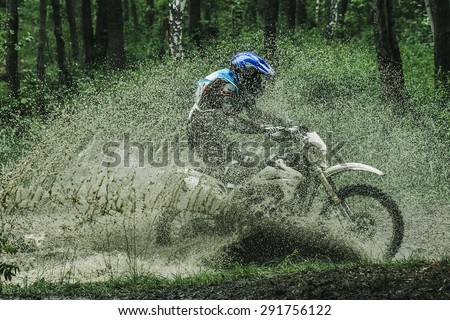 Motocross driver under the spray of mud - stock photo