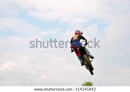 Motocross racer flies amid the clouds, rear view