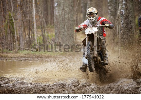 Motocross racer on wet and muddy terrain in Finland - stock photo