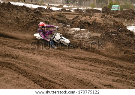 Motocross racer, with a large slope in gritty point-blank rotates on the motorcycle - stock photo