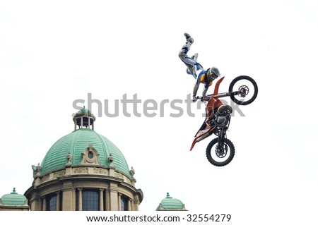 Motocross rider performing dangerous jumps with his bike isolated on white. - stock photo