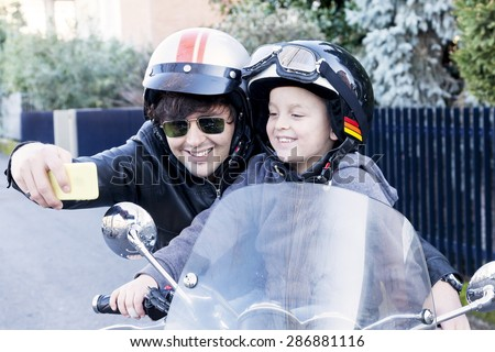 motor bikers father and son take a selfie on the road - stock photo