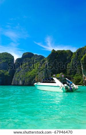 Motor boat on turquoise water of Maya Bay lagoon, Phi Phi island, Thailand - stock photo