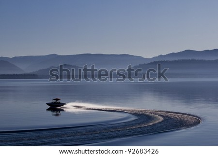 Motor-boat silhouette on lake Tahoe. Evening photograph of California lake with speed boat and foggy mountains on background. - stock photo