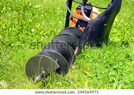 Motor earth auger on the grass