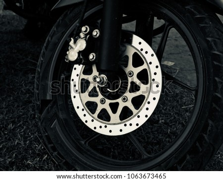 Motorbike front wheel with the disc brake isolated unique stock photograph