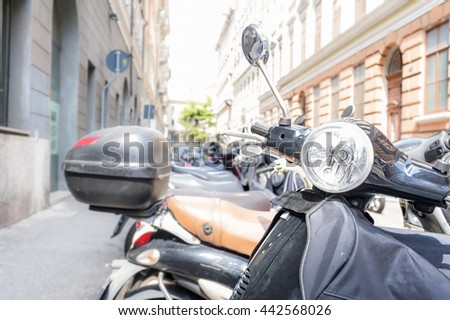 Motorbike, motorcycle scooters parked in row in city street. - stock photo