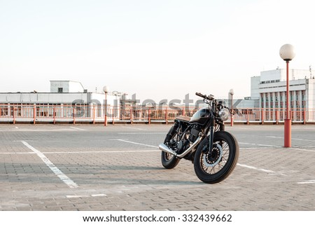 Motorbike on parking in city with open sky on background. Black vintage custom motorcycle - stock photo