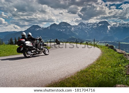 Motorbikes on the road in mountains with Alps in background.Salzkammergut,Austria. - stock photo
