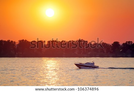motorboat at sunset - stock photo
