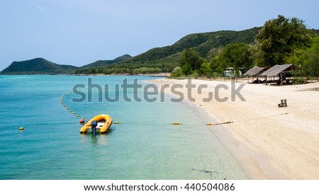 Motorboat docking beside the beach on mountain background - stock photo