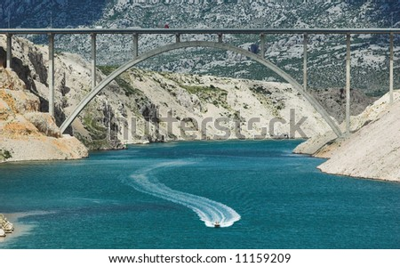 Motorboat in a bay sailing under a big highway bridge, horizontal frame - stock photo
