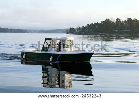Motorboat on calm water at dusk. - stock photo