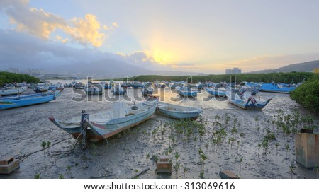 Motorboats stranded by riverside under a calm dawn ~ Scenery of sunrise with golden clouds and stranded fishing boats by the riverside during a low tide, in rural area of Taipei City, Taiwan - stock photo