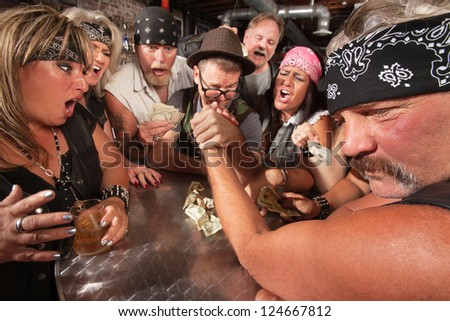 Motorcycle gang members arm wrestling with a nerd - stock photo