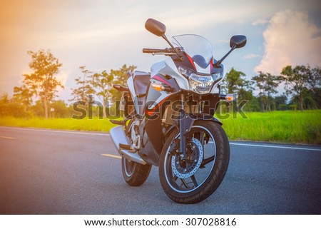 motorcycle on an empty road at sunny day - stock photo