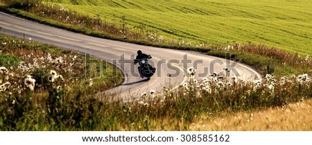 Motorcycle on the road at summer evening in Southern Finland.  - stock photo