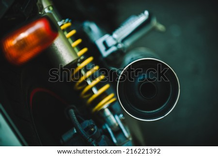 motorcycle parts close-up, shock spring and exhaust pipe - stock photo