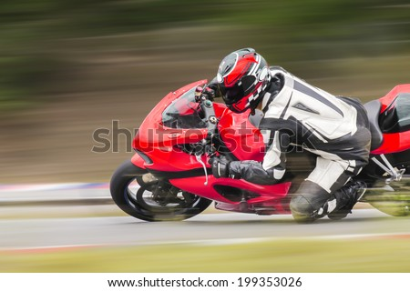 Motorcycle practice leaning into a fast corner on track - stock photo