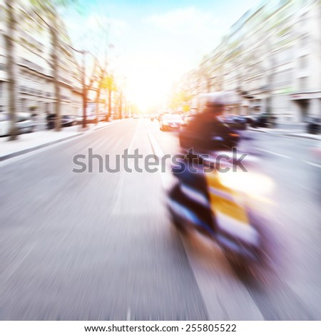Motorcycle rider on the street in motion blur during sunset. - stock photo