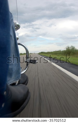Motorcycle Riders moving on an open road from a low perspective - stock photo