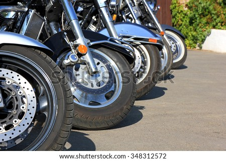 Motorcycles parked on a sunny summer day. Image close-up of the front wheels.