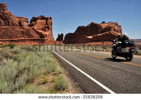 Motorcyclist entering Arches National Park - stock photo