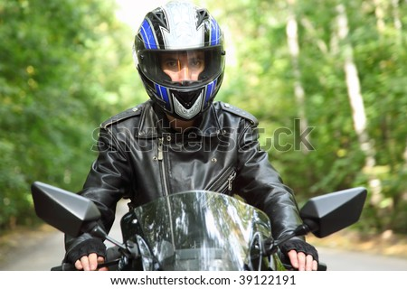 motorcyclist goes on road, front view, closeup - stock photo