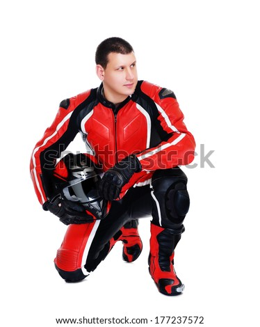 motorcyclist in red equipment standing on his knee looking to white area  - stock photo