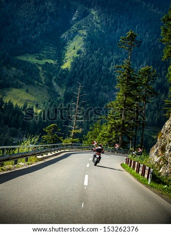 Motorcyclist on curves mountainous road, Alpine mountains, active lifestyle, driving  motorbike, beautiful green nature, speed concept - stock photo