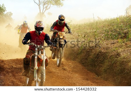 Motorcyclist on the competition at motorcycle race . The motorcycle race hole on December at Dambri waterfall, motorcyclist try to speed up goal, red soil way, indistinct dust - stock photo