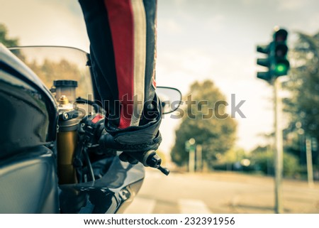 Motorcyclist on the road - Racing motorbike stops at traffic lights  - stock photo