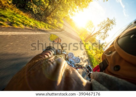 Motorcyclist riding motorbike in sunny morning - stock photo