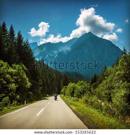 Motorcyclist riding on mountainous highway, Euro tour on motorbike, road pass along Alps mountains, extreme sport, freedom concept - stock photo