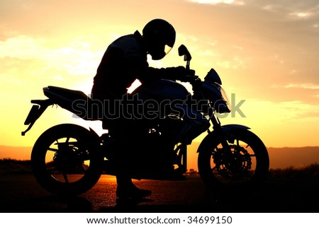 motorcyclist silhouette at the sunset - stock photo
