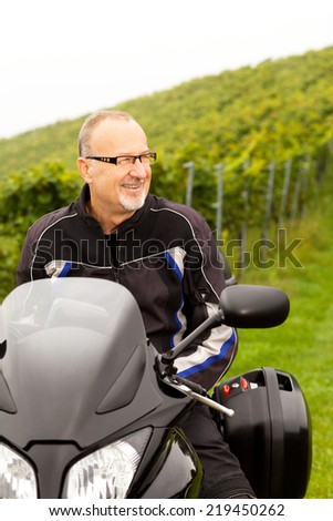 Motorcyclist sitting laughing on the bike - stock photo