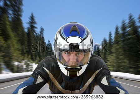 Motorcyclist soaring with his bike over a road in beautiful mountain scenics, surrounded by large pine trees and the melting snow in the warm spring sun - stock photo