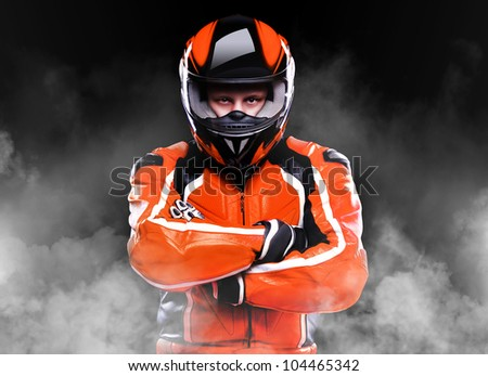 Motorcyclist standing in smoke on black background - stock photo