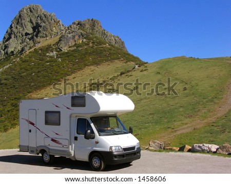 Motorhome parked at the mountain, near a rocky peak - stock photo