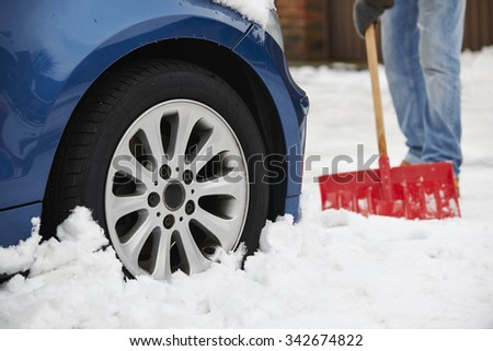 Motorist Digging Car Out Of Snow - stock photo