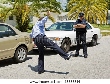 Motorist trying to walk a straight line while a police officer looks on. - stock photo