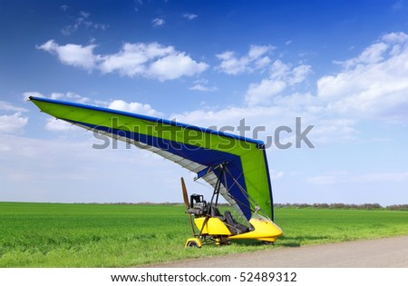 Motorized hang glider over green grass, ready to fly. - stock photo