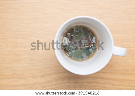 mouldy coffee tea cup on desk - stock photo