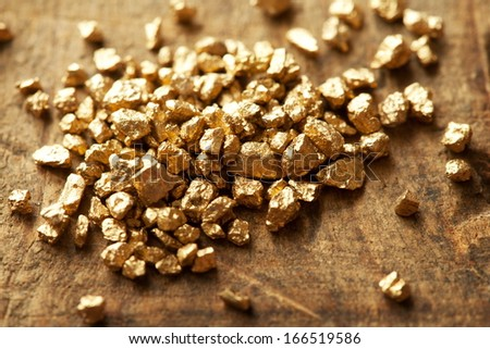 Mound of gold on a old wooden work table - stock photo